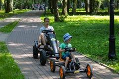Svetlogorsk, Russland - Juni 8,2019: Jungen, die vier-fahrbares Fahrrad im Stadtpark fahren lizenzfreies stockfoto
