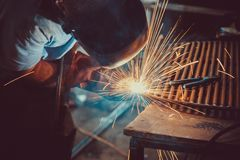 svetsande arbete Resa upp den industriella stålwelderen In Factory för tekniskt stål Arkivbilder