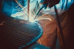 svetsande arbete Resa upp den industriella stålwelderen In Factory för tekniskt stål Arkivfoto