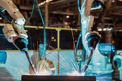 Svetsar industriella robotar för Closeuplag enhetsståldelen i bilfabrik Arkivfoto
