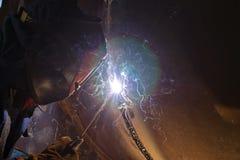Svetsning arbetar på metallvärmeexchangeren som använder manuell bågsvetsning Arkivbilder