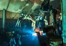 Svetsningrobotar bearbetar med maskin rörelse i en bilfabrik Arkivfoton