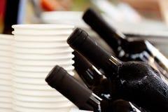 Svettiga flaskor av kylt vin och en bunt av pappers- vita koppar royaltyfri foto