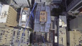 sview aereo del fuco 4k sulla grande città urbana moderna con il sito in costruzione dei grattacieli alti con le gru sulla cima archivi video