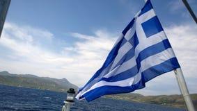 Sviluppandosi nella bandiera del vento della Grecia sui precedenti della costa retrocedere fotografie stock libere da diritti