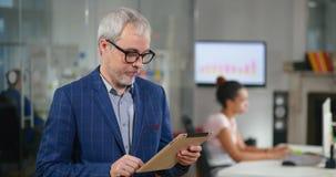 Sviluppatore senior che utilizza il computer della compressa per il monitoraggio di software nell'ufficio della società di tecnol stock footage