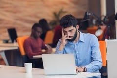 Sviluppatori di software che si siedono con il computer portatile in ufficio startup Fotografia Stock Libera da Diritti