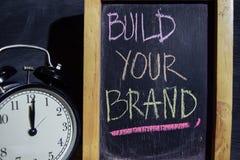 Sviluppi la vostra marca su scritto a mano variopinto di frase sulla lavagna fotografia stock