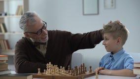 Sviluppo infantile, nipote d'istruzione di prima generazione per giocare scacchi, svago della famiglia archivi video
