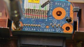 Svitatura della vite Una mano che tiene un cacciavite è installante o riparante le componenti di computer archivi video