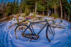 SVOLVAER, ISLAS DE LOFOTEN, NORUEGA - 10 DE ABRIL DE 2018: Vista al aire libre de bycicles viejo-oxidado-abandonados en la nieve  Imagen de archivo libre de regalías