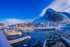 SVOLVAER, LOFOTEN ISLANDS, NORWAY - APRIL 10, 2018: Outdoor view of Fishing boat in harbour with some building behind. And huge mountain covered with snow in Stock Photo