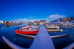 SVOLVAER, LOFOTEN ISLANDS, NORWAY - APRIL 10, 2018: View of red fishing boats in harbour with buildings in the horizont. In a gorgeous blue sky and sunny day Stock Photo