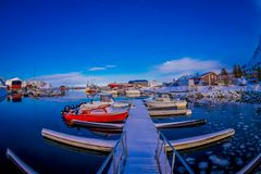 SVOLVAER, LOFOTEN ISLANDS, NORWAY - APRIL 10, 2018: View of red fishing boats in harbour with buildings in the horizont. In a gorgeous blue sky and sunny day Stock Photography