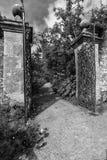 Svärtar den i naturlig storlek trädgårds- porten för gammal smidesjärn och tegelstenväggen in a Arkivfoto