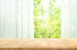 Svuoti del piano d'appoggio di legno su sfuocatura della tenda con verde di vista della finestra dal fondo del giardino dell'albe immagine stock libera da diritti