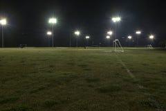 Svuoti i campi di calcio atletici alla notte con le luci sopra Fotografie Stock