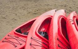 Svuoti i kajak ricreativi di plastica rossi per affitto o noleggio, immagazzinati sulla spiaggia sabbiosa dopo le ore un giorno p immagine stock libera da diritti