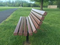 Svuoti il banco di parco di legno circondato da erba verde e dagli alberi Immagini Stock