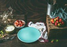 Svuoti il piatto blu sul tavolo da cucina di legno rustico scuro con le fragole ed il yogurt in ciotole Fondo stile country dell' immagine stock