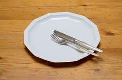 Svuoti il piatto di cena bianco con il coltello e la forcella Immagini Stock