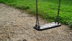 Svuoti il sedile dell'oscillazione che ondeggia al campo da giuoco nel parco Fotografie Stock Libere da Diritti