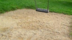 Svuoti il sedile dell'oscillazione che ondeggia al campo da giuoco nel parco Immagini Stock