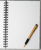 Svuoti l'anello in bianco, il blocchetto per appunti a spirale, una penna dell'oro Fotografia Stock Libera da Diritti