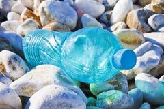 Svuoti la bottiglia di plastica verde abbandonata sulla spiaggia della ghiaia Immagine Stock