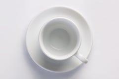 Svuoti la chiara tazza di caffè sul piattino contro fondo bianco, vista superiore Immagini Stock Libere da Diritti
