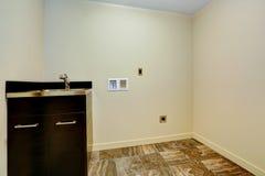 Svuoti la nuova stanza di lavanderia con il lavandino ed il gabinetto. fotografia stock