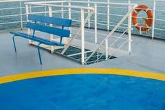 Svuoti la piattaforma superiore con il banco di legno blu ed il punto di raccolta dell'elicottero sul traghetto greco fotografie stock libere da diritti