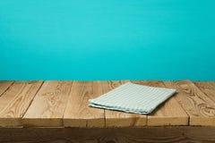 Svuoti la tavola d'annata di legno con la tovaglia sopra il fondo blu della parete fotografia stock libera da diritti