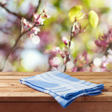 Svuoti la tavola di legno con la tovaglia sopra il fondo del bokeh del giardino della molla per il montaggio del prodotto immagine stock libera da diritti