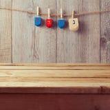 Svuoti la tavola di legno della piattaforma con la trottola del dreidel di Chanukah che appende sulla corda Fotografie Stock