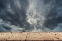 Svuoti la tavola di legno e le nuvole drammatiche di temporale al cielo scuro Immagini Stock Libere da Diritti
