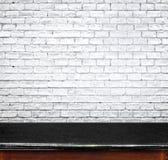 Svuoti la tavola di marmo nera ed il muro di mattoni bianco nel fondo pro Immagine Stock