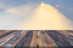 Svuoti la tavola o la plancia di legno con i raggi di sole o i raggi di sole della luce del sole dal fondo delle nuvole Immagine Stock