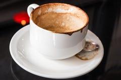 Svuoti la tazza da caffè utilizzata con le macchie sulla tavola di vetro Fotografia Stock