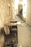 Svuoti la via stretta di vecchia città con le tavole di caffee all'aperto. Fotografia Stock