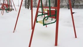 Svuoti le catene metalliche dell'oscillazione nell'orario invernale con neve archivi video