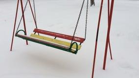 Svuoti le catene metalliche dell'oscillazione nell'orario invernale con neve stock footage