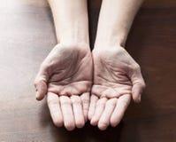 Svuoti le mani femminili che giudicano qualche cosa di rotondo a offe Fotografia Stock