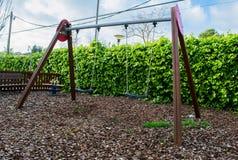 Svuoti le oscillazioni con le catene che ondeggiano al campo da giuoco per il bambino Fotografia Stock