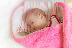 Swaddled adorable newborn girl is sleeping in bed Stock Images