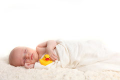 Swaddled Infant Holding a Rubber Duckie Stock Photo