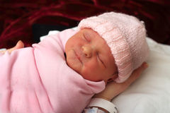 Swaddled Newborn. A close-up portrait of a sleeping bundled newborn baby wearing a pink knitted cap. Shallow depth of field Stock Photo