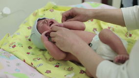 Swaddling a newborn. Woman hands are swaddling a newborn boy. Diapers, blanket. Maternity hospital stock footage