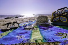 Swag στην παραλία με τα προστατευτικά δίοπτρα καπέλων παντοφλών και μια τσάντα στοκ εικόνες