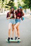 Swag girlfriends standing on skateboard and posing at street. stock photo